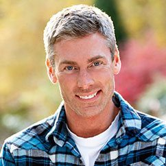 Man in plaid shirt smiling outside
