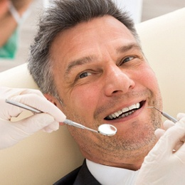 An older man lying back in a dentist's chair in preparation tooth-colored fillings in Arlington