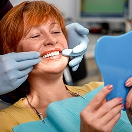Woman with dental implants looking at her smile in mirror