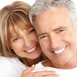 Couple smiling after dental implant tooth replacement