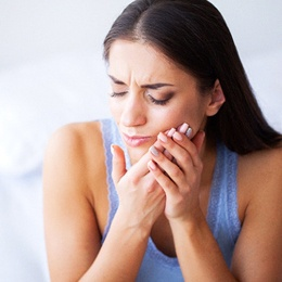 A young woman sitting on her bed and holding her cheek in pain and needing root canal therapy in Arlington
