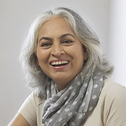 An older woman wearing a polka dot scarf and smiling after undergoing a root canal