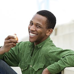 Young man smiling in green shirt eating apple