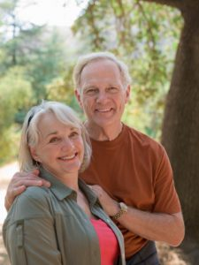 Senior couple smiling with secure dentures thanks to the dental implants arlington patients love