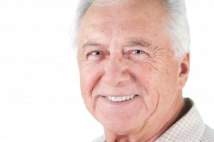 older man with dentures smiling
