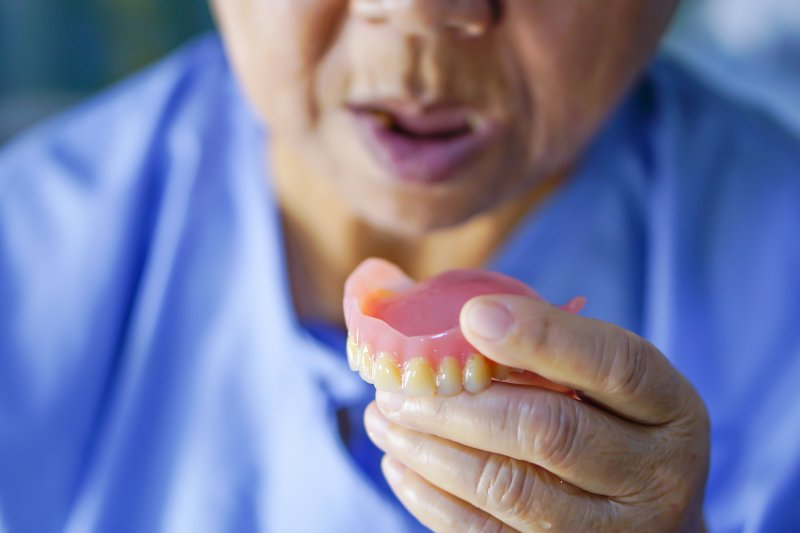 an older man holding his denture in his hand