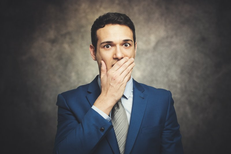 a man dressed in a suit and covering his mouth because he is embarrassed by his smile and breath