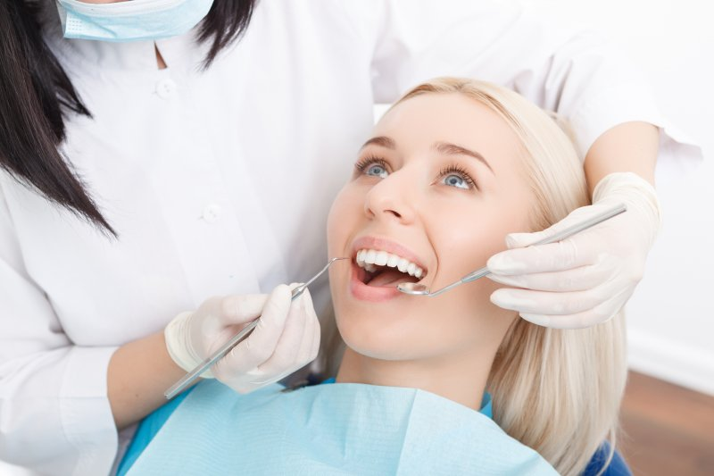 a young female with blonde hair having a dental checkup performed by her dentist