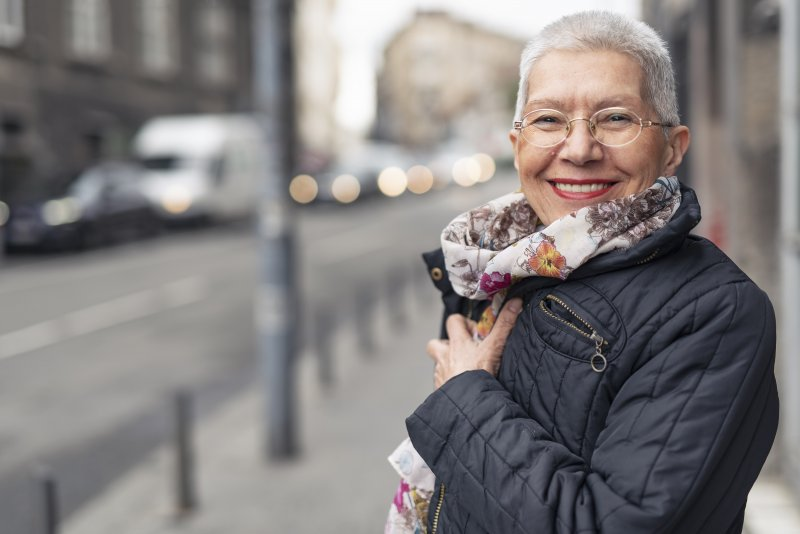an older woman wearing a scarf and coat while standing outside and smiling