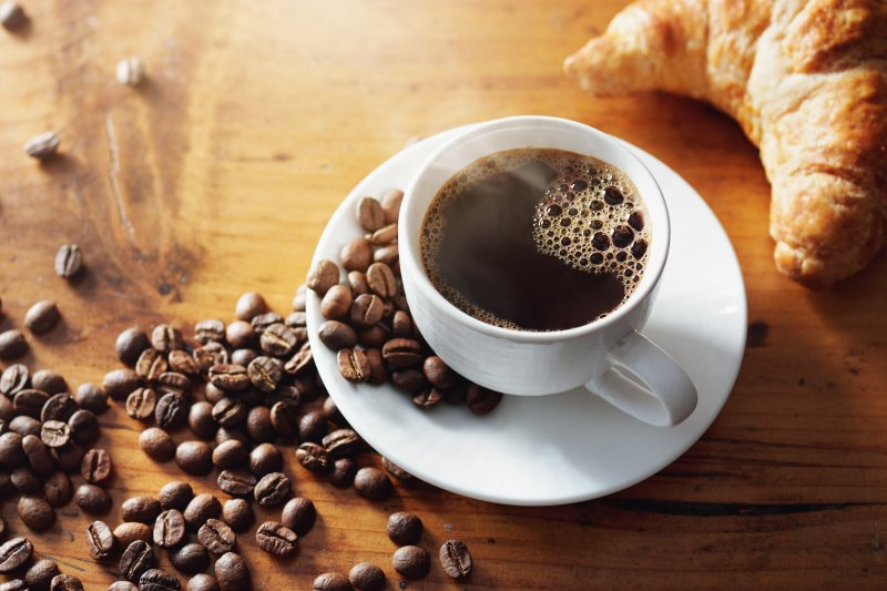 a cup of hot coffee and a croissant