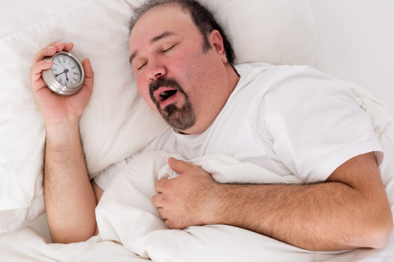 a man holding a small clock in his hand while asleep with his mouth open