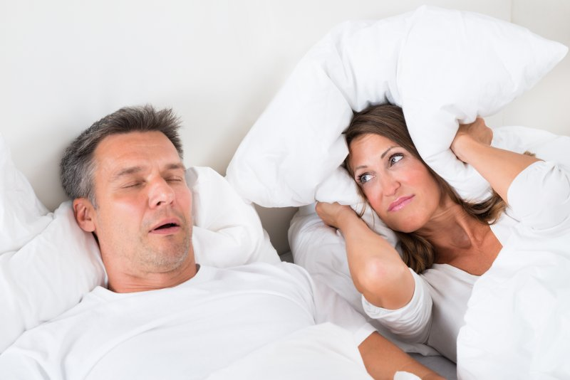 a man snoring while a woman lying next to him covers her ears with a pillow