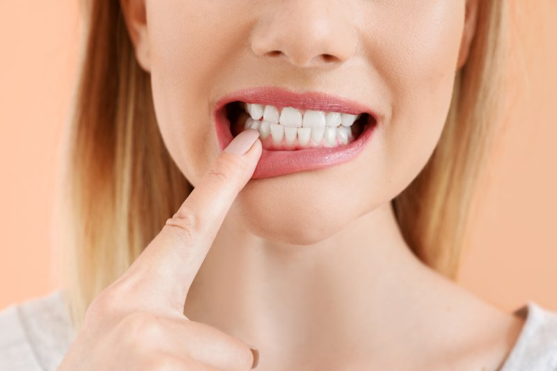 woman pointing to her tooth in Arlington